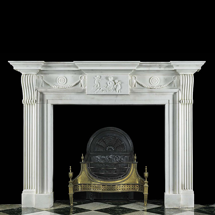 12479: A substantial and finely proportioned late Georgian antique fireplace mantel. Beautifully carved in white statuary marble with a breakfront shelf over the grandly carved frieze centred by a figural pl