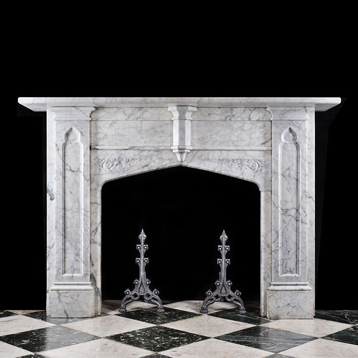 12548: An imposing Victorian Neo Gothic Chimneypiece mantel in lightly veined English Marble with a half hexagonal column plinth centrally on the frieze and inset Gothic tracery panelled jambs supporting the