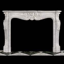 12672: A finely carved Statuary Marble French Louis XV Rococo style chimneypiece, with an elaborate central stylised shell cartouche surrounded by delicate flowers and foliage on the scrolled frieze and with