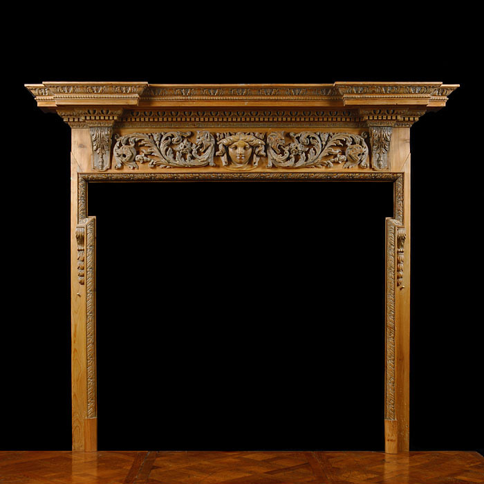 12713: A tall carved pine chimneypiece in the style of William Kent, with a prominent shelf above a frieze profusely carved with scrolling acanthus centred by a female mask.  Late 19th century.  Link to a se