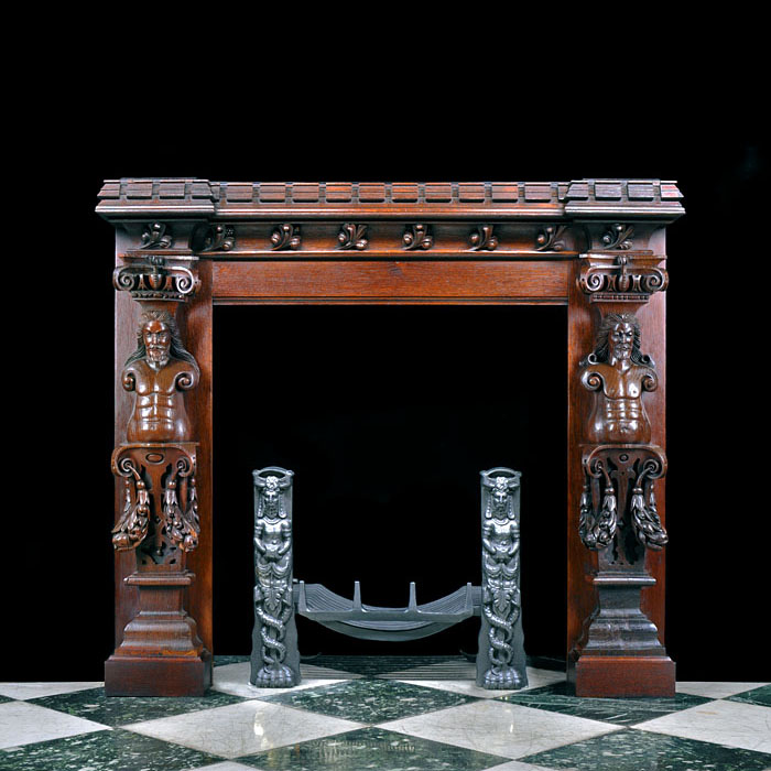 12794: A small decoratively carved oak fireplace in the Jacobean Revival manner with a substantial castellated shelf and later top, bold carved leaf adornment on the frieze, a pair of bearded caryatid on the