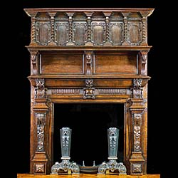 13001: A finely carved small oak fireplace and overmantel in the Jacobean Revival manner. The galleried overmantel set with six panelled niches separated by barley twist columns above two original inlaid mar