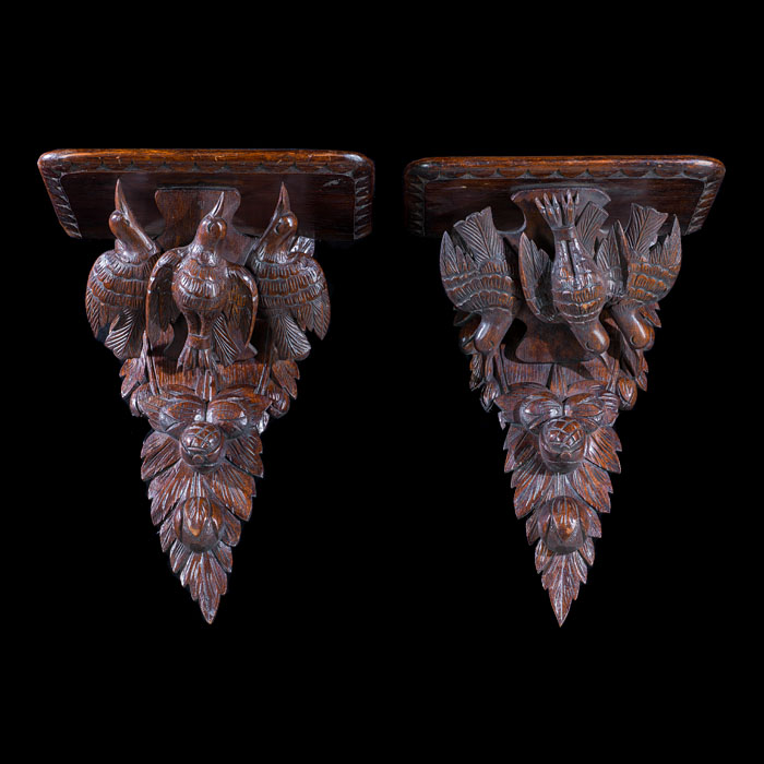 A near pair of Edwardian oak wall brackets