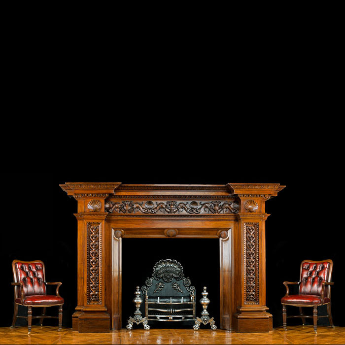 13011: An enormous and grand antique walnut chimneypiece in the Neoclassical style. The frieze elaborately carved with three pairs of sea serpents alternating with flambeau urns and scallop shells. The shell