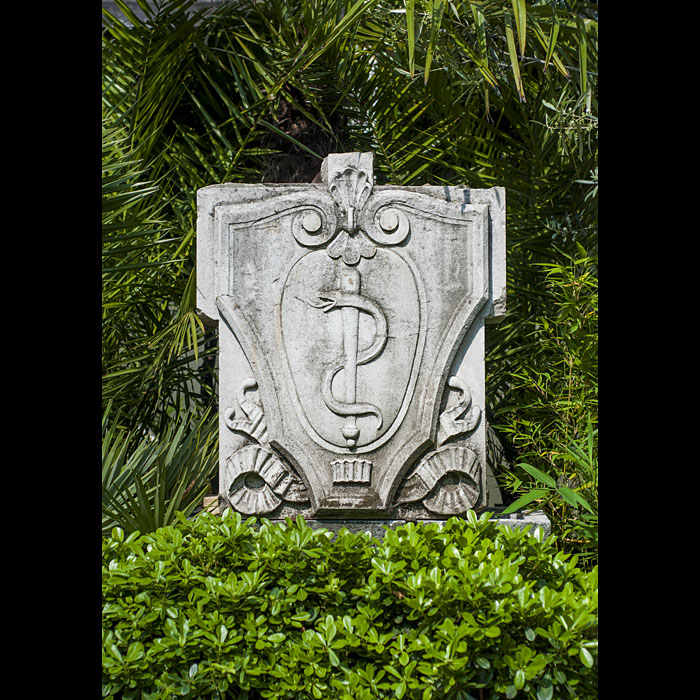 13143: One of five Portland Stone Plaques removed from the facade of St Thomas' Hospital in London. Carved in the shape of a shield it bears a serpent entwined round a staff representing the Rod of Asclepius