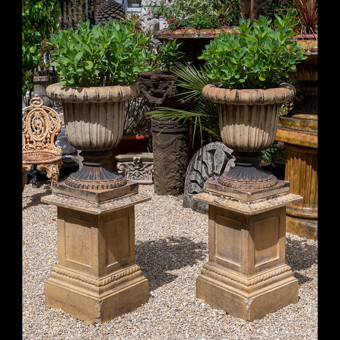 13151: A pair of terracota Campagna urns, with scallop fluted edging and sides, on large  plinths.