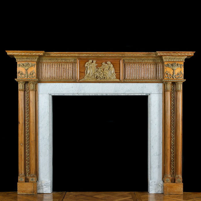 13154: A grand and large George III twin columned warm toned pine and gesso Georgian chimneypiece with its original Carrara Marble slips. The fluted and athemion decorated frieze is centred by a plaque depic