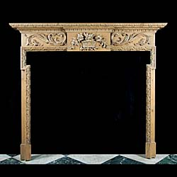 13232: A small and compact 20th centruy Georgian style dog leg pine fireplace, carved along the frieze with large scrolled acanthus leaves, flanking the highly carved central plaque depicting a wicker basket