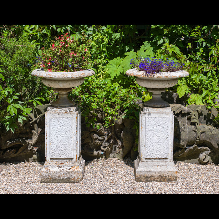A pair of Antique cast iron garden urns on intergral plinths