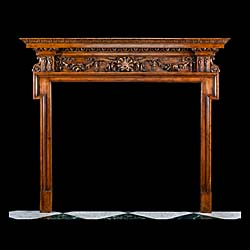 13331: A tall carved pine fireplace surround, in the George III manner, with a highly carved frieze of griffins, fruits and swags. Originally with coloured marble slips which we can supply in antique green C