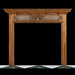 13332: A carved pine Neoclassical style fire surround with a central vase of flowers on a finger fluted frieze with paterae on the endblocks and acanthus leaf carving around the opening. English early 20th c