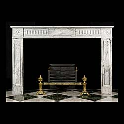 13338: A finely carved French Regency fireplace in Arabescato Marble, with a fluted frieze and a central ribboned leaf plaque, stylised leaf endblocks and tasselled leaf strapped decoration descending the ja