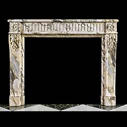 13427: A Louis XVI fireplace surround in Pavonazzetto marble, with a finger fluted frieze and floral paterae endblocks and scrolled acanthus corbels above fielded jambs. Also shown with the original insert,