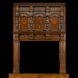 13438: A large and highly carved oak chimneypiece in the English Jacobean manner. The overmantel set with three arched marquetry floral panels flanked by four figural columns.The fireplace frieze decorated w