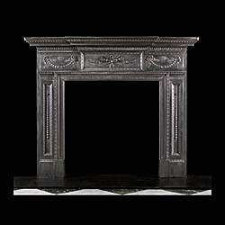 13454: A substantial cast iron Neoclassical style fireplace, with a large central plaque of quivers, arrows and wheatsheafs, flanked by festoons and with descending bellflowers on the panelled jambs. English
