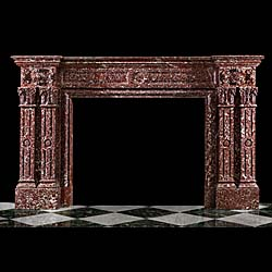13463: A substantial and grand Palladian style antique Chimneypiece in Rouge Langedoc marble, the endblocks carved with strapwork designs flanking a simple panelled frieze. The jambs resting on sturdy footbl