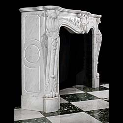 13503: A substantial veined statuary white marble Rococo style fireplace in the Louis XV manner, with a highly carved cartouche flanked by trailing blossoming vines, the endblocks with deep scrolls above ang