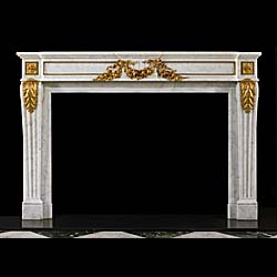13513: A large and impressive Louis XVI antique fireplace mantel in white statuary marble, with a gentle breakfront shelf. The frieze decorated with very fine quality gilt-bronze ormolu swags repeated in the