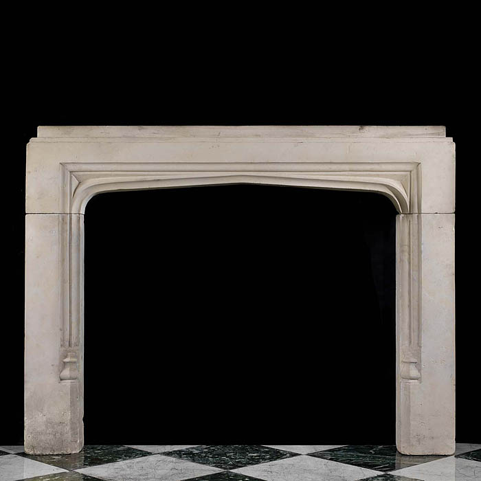 13530: A Tudor style  arched limestone fireplace of beautiful proportion with an unusual stepped rectangular mantel, cavetto moulding, starpoint spandrels and bosses to the aperture.English late 19th century