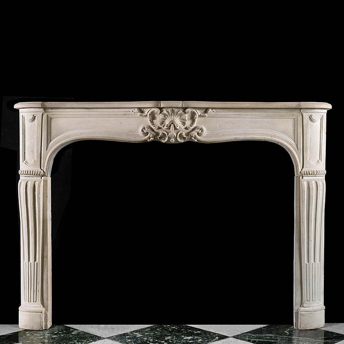 An antique Rococo style limestone fireplace surround in the Louis XV manner
