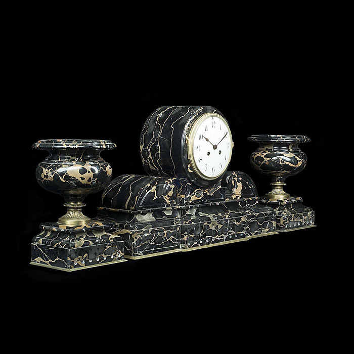 13555: A Neoclassical style mantelpiece clock in black and gold Portoro marble with brass detail paired with twin urn vases. The simple white enameled clock face with Arabic numerals, the whole resting on a