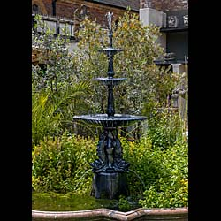13582: A tall and slender 20th century black painted cast iron three tier fountain in the Coalbrookdale manner, with triple graduated bowls of campana form, the water spouts emanating from the top finial and