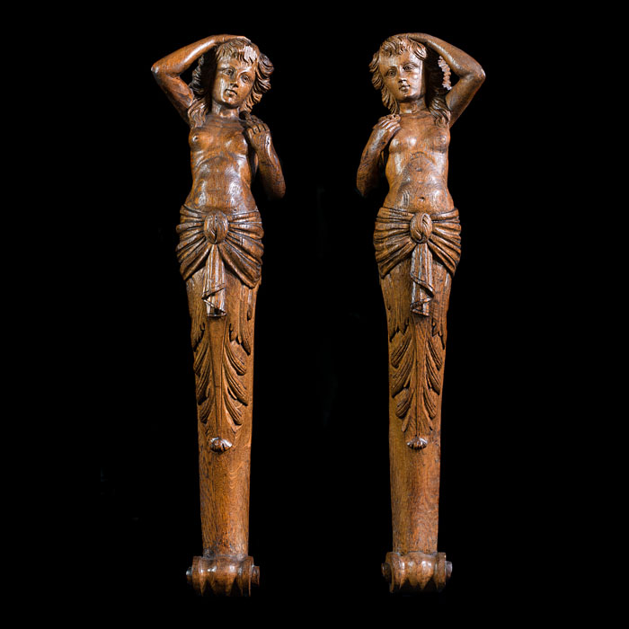 A pair of carved oak female caryatids