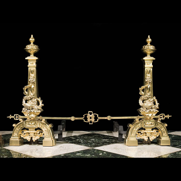 An antique pair of brass dragon andirons and fender bar