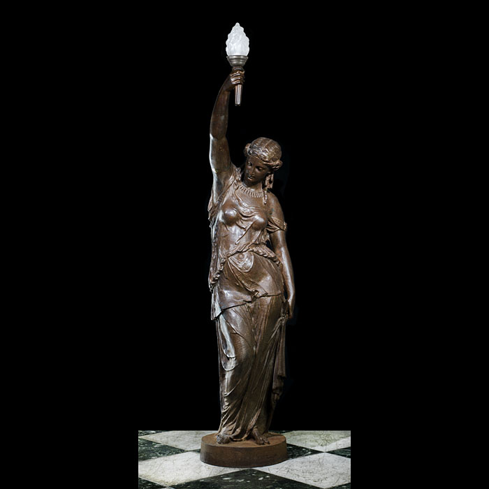 13747: A tall patinated cast Iron statue of a Neoclassical maiden bearing a torch aloft reminiscent of the 'Statue of Liberty' the design of which was based on the concept of the goddess Liberty which dates