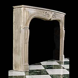 An antique rococo style limestone fireplace surround