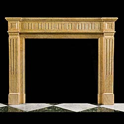 13788: A simple Louis XVI French Regency style antique carved Crema Valencia marble chimneypiece with a fluted frieze, plain endblocks and stop fluted jambs. French late 19th century.