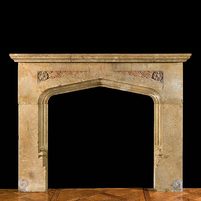 13796: An early 20th century large Tudor style carved warm coloured stone fireplace surround, with fine Tudor Rose and foliate carving recessed into the spandrels and with a slow pointed arched opening typic