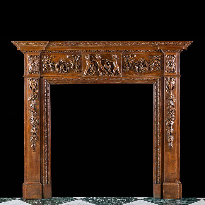 13801: A highly decorative carved pine chimneypiece mantel in the George III style.  The central plaque on the frieze, depicting three putti carrying a deer, is flanked by floral and fruiting swags. The twin