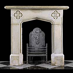 13811: A small Tudor Revival Chimneypiece carved in distressed limestone the simple shelf above a gentle Tudor style arched opening flanked by a pair of quatrefoil each with stylised foliate decoration, the