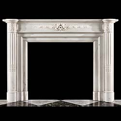 13856: A finely carved Louis XVI style chimneypiece in statuary marble. The moulded shelf is supported on stop fluted half columns with carved acanthus leaf capitals, flanking the panelled frieze, centered w