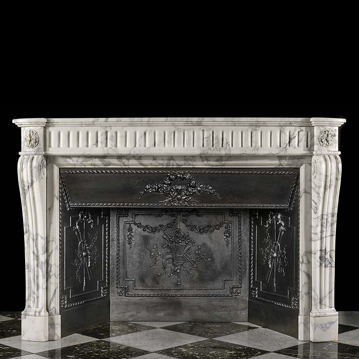 13866: A French Louis XVI style chimneypiece in boldly veined statuary marble. The bow fronted fluted frieze is flanked by floral paterae endblocks, supported on moulded scrolled jambs. The original panelled