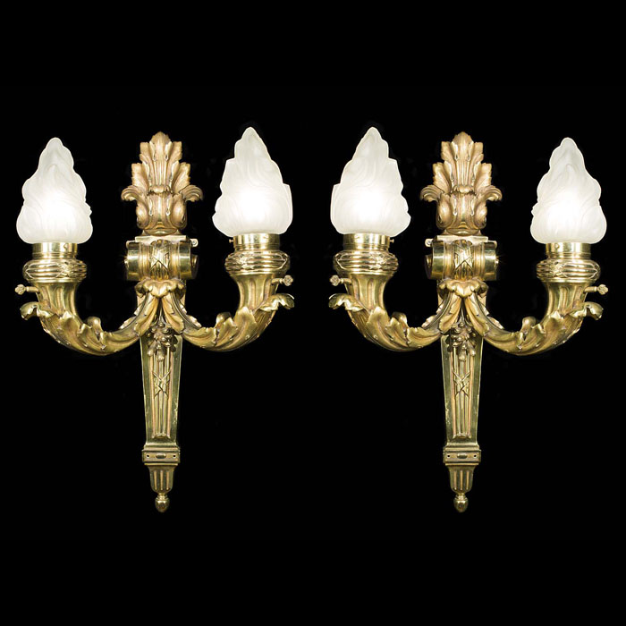 A pair of large Baroque flambeau wall lights