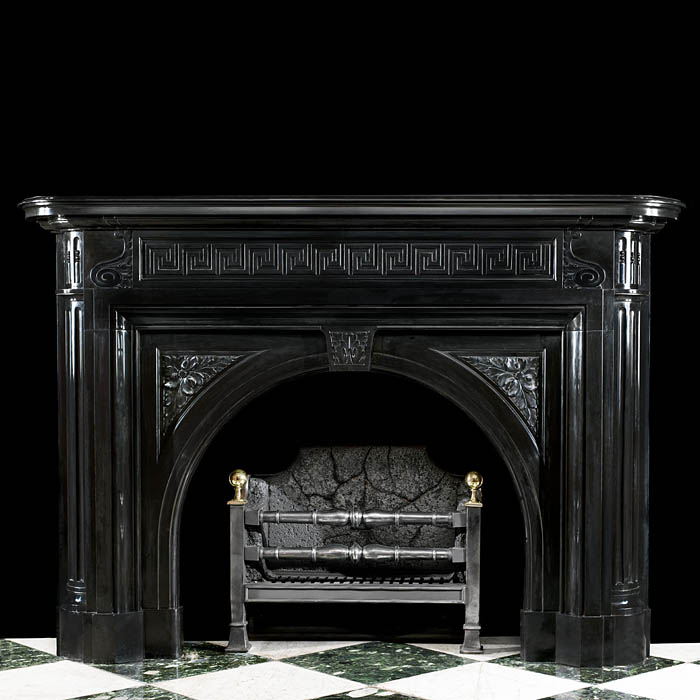 13976: An antique Belgian black marble Louis XVI style arched Chimneypiece.The Greek key pattern frieze with carved scrolling acanthus leaf ends,is set below the generously and deeply moulded shelf. The arch