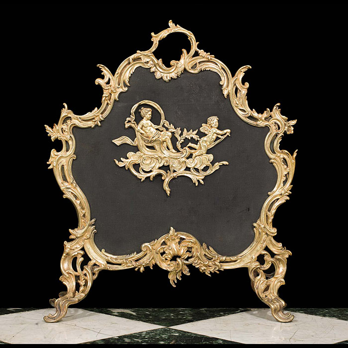 13988: A fine example of a brass and mesh Rococo antique firescreen or spark guard, both solid and heavy embellished with cherubs and framed within an elaborate scrolling foliate decoration.French mid 20th c