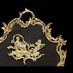 A Rococo style brass and mesh fire guard