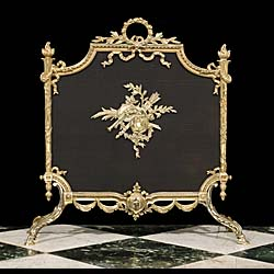 14042: A gilt brass & mesh Louis XV style fire screen. The elaborately ornate frame topped with flambeau finials and a floral wreath handle, the bottom centred by a medallion,  the whole supported on two pai