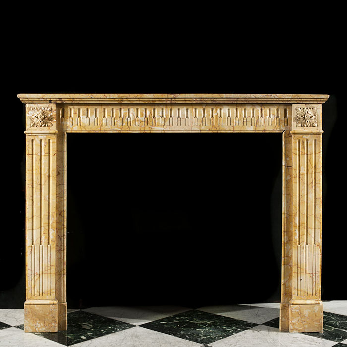 14067: An antique Louis XVI style chimney piece in Crema Valencia marble, with a fluted frieze flanked by square floral end-blocks, over stop fluted jambsFrench late 19th century.