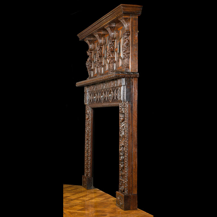 A relatively small carved oak Jacobean style antique fireplace surround.