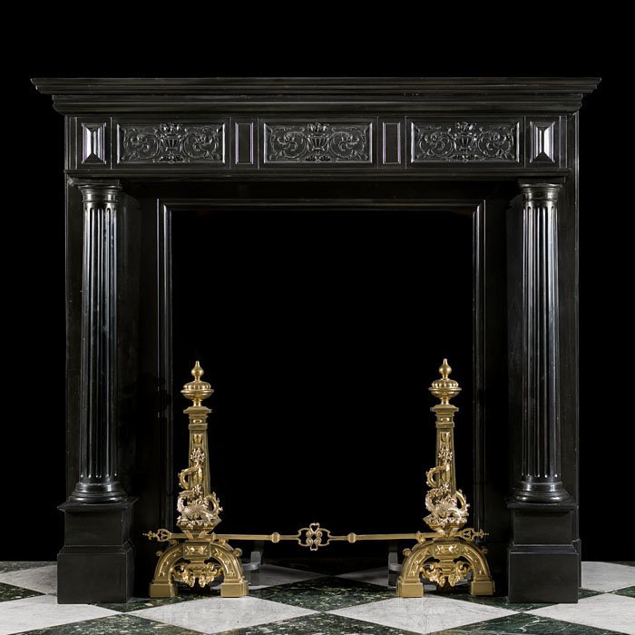 14307: A smart High Renaissance style polished Belgian Black marble fireplace mantel, with three foliate carved panels on the frieze flanked by a pair of lozenge endblocks set above tapering free standing fl
