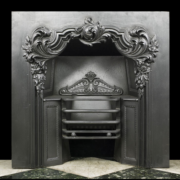 An antique cast iron Victorian fireplace insert