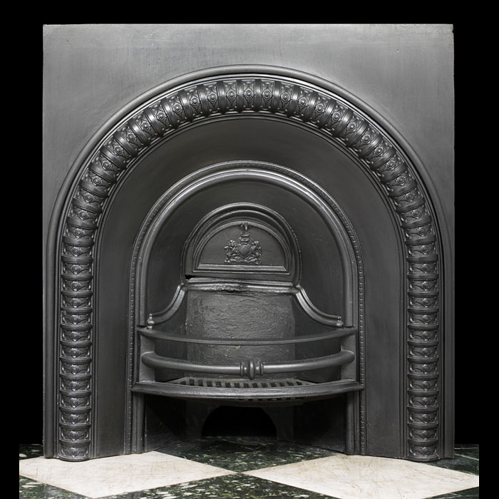 A Victorian small arched fireplace insert with an integral grate