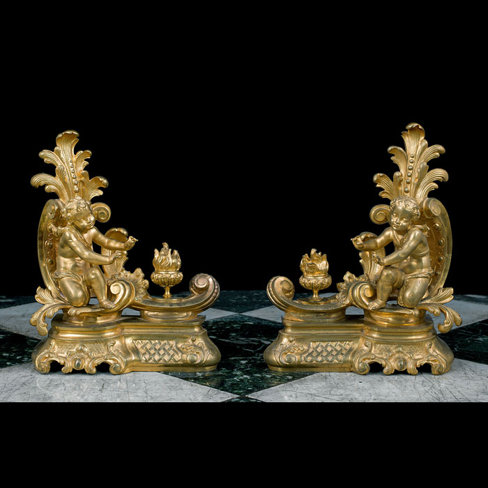 A pair of Rococo style cherubic gilt bronze antique chenet