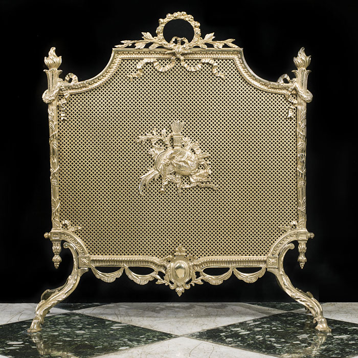 A Louis XVI Regency style gilt brass and mesh firescreen