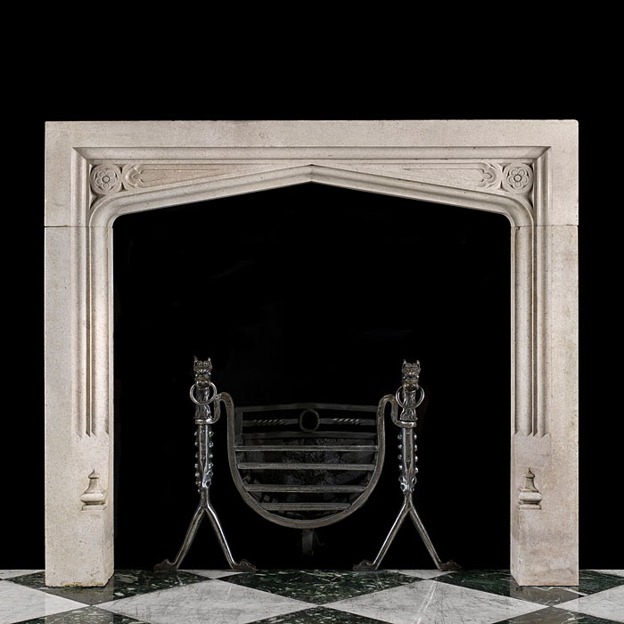 14531: A 19th century polished Portland Stone Tudor/Gothic Revival fireplace surround with the typical slow pointed arched opening beneath finely carved rosette and panelled detail the plain jambsterminating