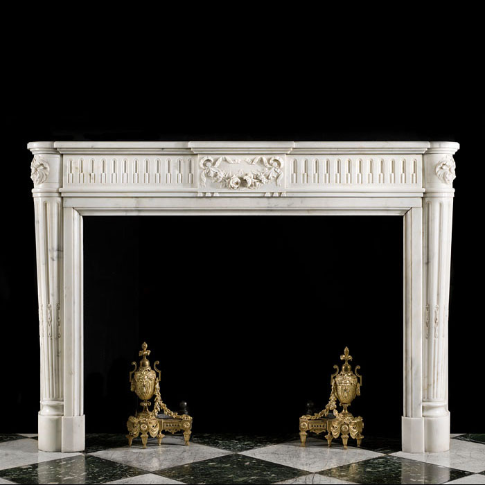 An antique French Louis XVI style carved statuary marble fireplace.